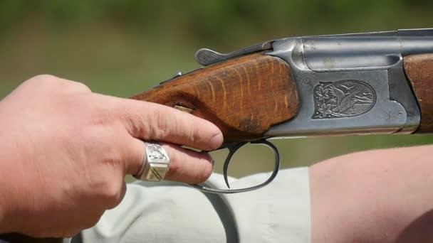 Sportliche Flinte schießen aus männlichen Händen an einem sonnigen Tag im Sommer A markante Höhenplan der männlichen Hände halten eine Jagd Schrotflinte, mit dem Ziel und Auslöser schnell an einem sonnigen Tag im Sommer