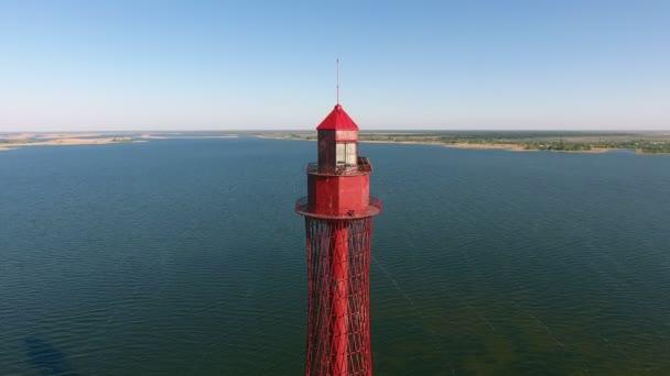 Luftaufnahme eines riesigen roten Leuchtturms auf dem Schelfeis des Schwarzen Meeres in der Ukraine bei Sonnenuntergang ein Blick aus der Vogelperspektive auf den hoch aufragenden roten Leuchtturm aus metallischen Gittern auf der Schwarzmeerschwärme bei goldenem Sonnenuntergang im Sommer. die Küste ist in der Kulisse