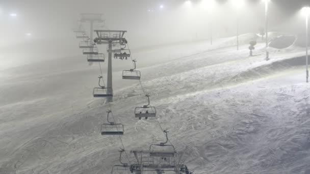 Hohe Skilift ohne Touristen bewegen sich in Levi Skigebiet in Finnland in schneebedeckten Winter verträumten Blick auf einen hohen Skilift ohne sitzende Skifahrer in Levi Skigebiet in Finnland im Winter hinauf. zwei Reihen beleuchteter Laternenpfähle sind entlang des Platzes aufgestellt.