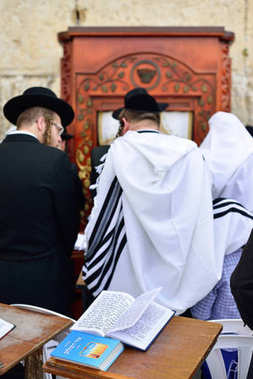 JERUSALEM, ISRAEL - APRIL 2017: Talmud Tora Tanach Books lying on table during prayer in Bar Mitzwa Ceremony at the Western Wall Jerusalem (Kotel) with people in the background