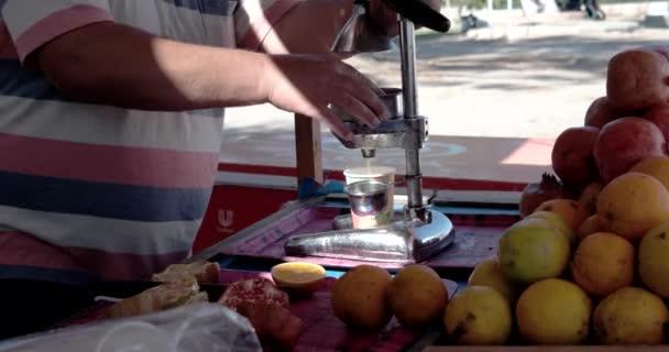 Close up of Man Using Old Fashion Juicer to Make Orange Juice