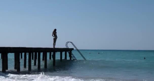Dospívající dívka skákání z mola do moře