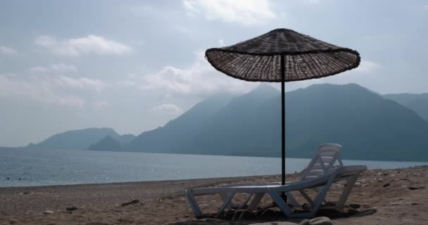 Sonnenschirm und Liegestühle am Strand im Zeitraffer