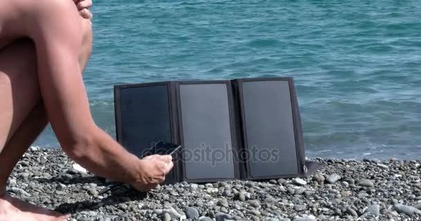 Muž obvinění mobilní telefon s osobní solární Panel na mořskou pláž