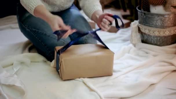 Mladá žena doma balení vánočních dárků s balicího papíru
