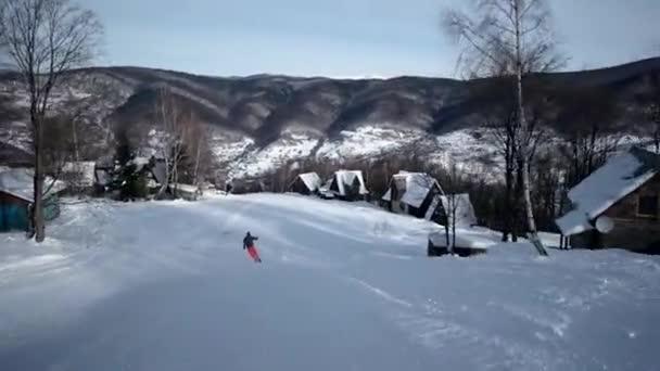 Pohled zezadu na vyřezávání profesionální lyžař po zasněženém svahu