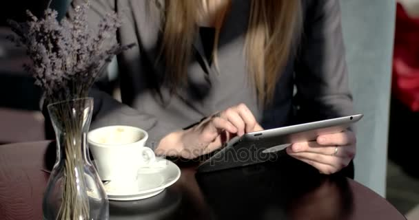 Young Business Woman Sits at a Table Drinking Coffee, Tea and Using Tablet Computer Typing on Tablet pc in a Coffee Shop, Restaurant