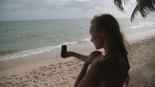 Tengerparti nyaralás emberek - nő fehér fürdőruha teszi selfie pihentető, tökéletes paradicsomi tenger nézett. Lány a bikini napozásra a nyaralás utazás lassított lövés