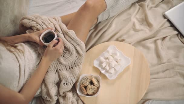 woman in warm sweater on the bed with cup of coffee in hands, Christmas tree new year the top point shooting