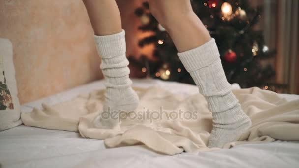 Žena v teplé ponožky na posteli, nohy střílet closeup vánoční stromeček nový rok