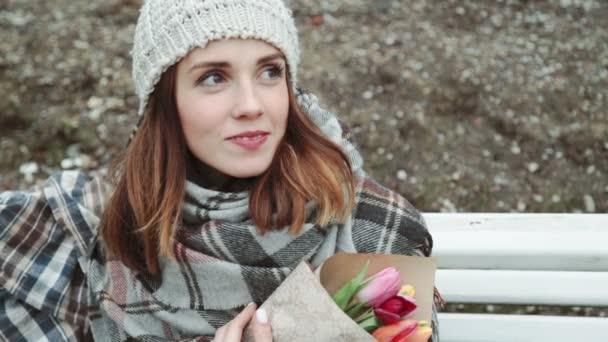 Mladá žena sedící na lavičce kytice květů tulipánů v ruce detail, chladné počasí, bílá