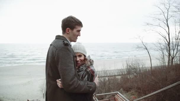 Mladý pár při pohledu na moře, objetí na pláž, kabát a klobouk, Baltské nebo Island chladné počasí