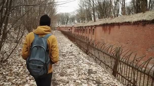 Mladý muž s batohem na zádech procházky parkem na jaře nebo na podzim stromy žluté listy, vedle opuštěné německé pevnosti, cihlové zdi, Starý Železný plot