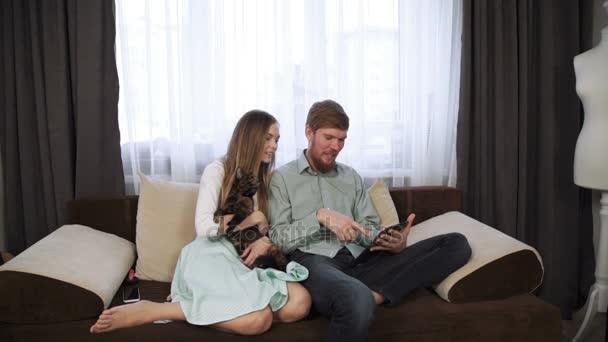 Paar sitzt auf der Couch Sofa zu Hause Look in der Tablette und Lächeln, trinken Tee aus einem weißen Tee-Set und vor dem Fernseher.