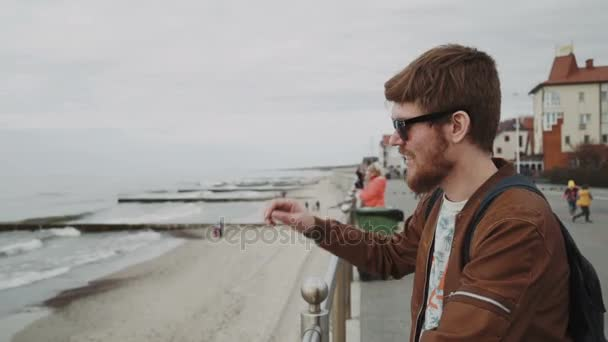 A fashionable young man with a red beard, in a brown leather jacket, wearing sunglasses With a backpack, smiles and looks at the sea