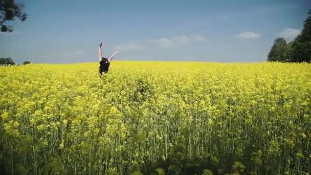 Mladá žena v černém oblečení kombinézy přes žluté pole dotýká květiny Hd
