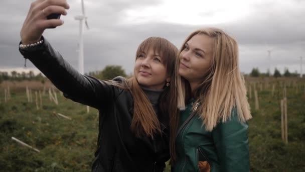 Two girlfriends make selfie outdoors