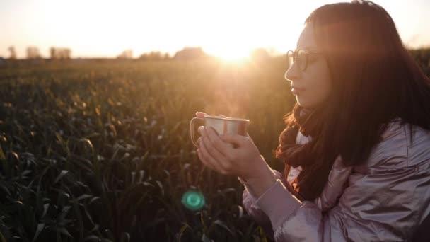 Mladá žena s brýlemi vychutnat pití horkého čaje venku detailní