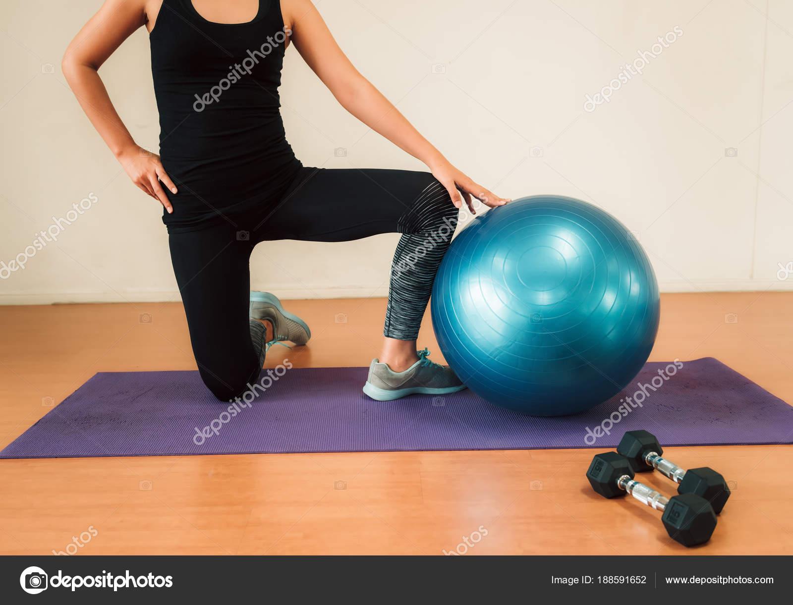 Mujer asiática ejercicio con bola de la yoga en la gimnasio e3bc0e631b7d