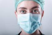 Női orvos védő maszk és orvosi sapka izolált háttér, Closeup portré orvosi sebész orvos visel orvosi maszk másolási hely. Klinikai egészségügyi ellátás / orvosok foglalkozása