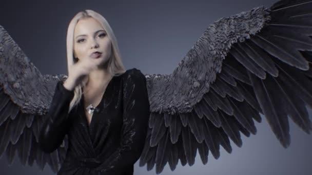 Szőke lány, egy fekete ruha és szárnyakkal