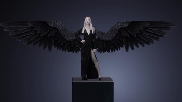 Blond dívka v černých šatech a s křídly