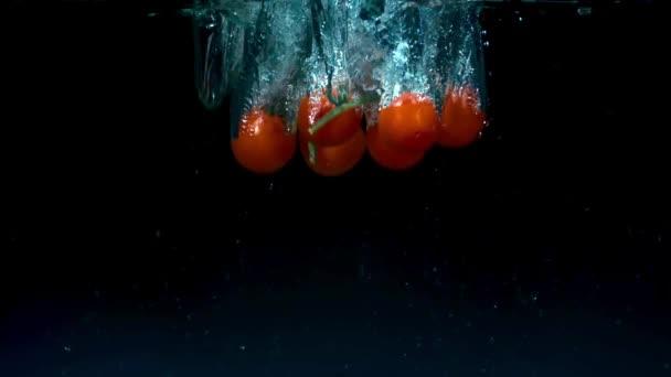 Rajčata v pomalém pohybu, plovoucí ve vodě