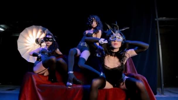 Tři dívky v maskách na pohovce pózuje ve fotografii