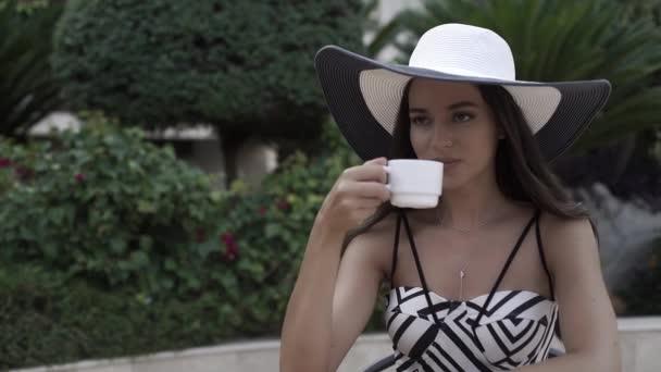 Elegantní dívka v klobouku pití čaje u stolu