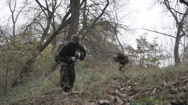 Paintball hráčů bouře v lese v pomalém pohybu