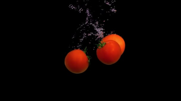 Falling tomatoes in water in slow motion