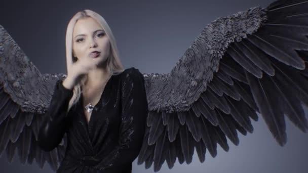 Gyönyörű lány egy ruhában, fekete szárnyak