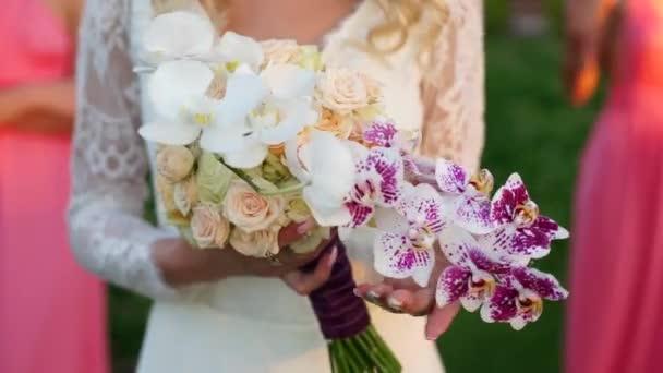 Nevěsta se dotýká rukama kytici růží a orchideí, družičky připravit.