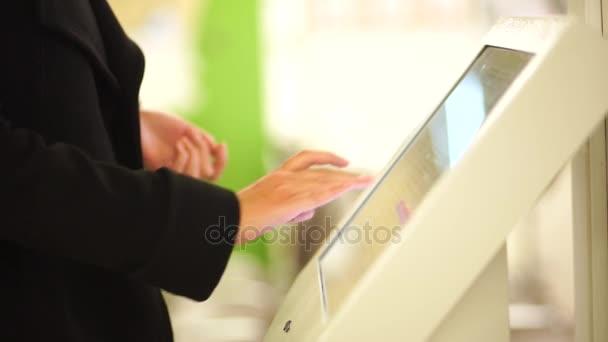 Na podzim oblečená žena pomocí terminálu vlastní služby zaplatit jízdné