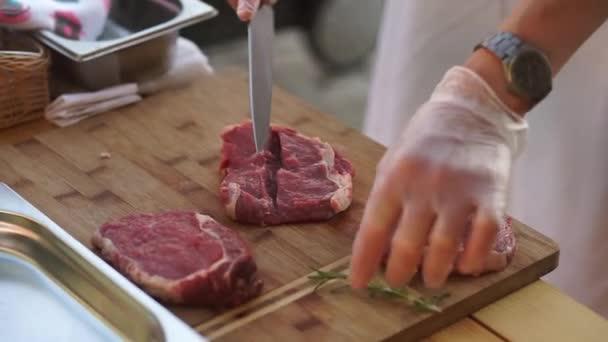 Kuchař dělá steaky s rozmarýnem.