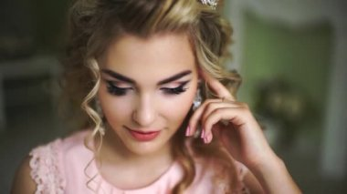 Beautiful Young Bride. Stylish Woman Fiancee with Bridal Hairstyle, Event Makeup and Jewelry. He looks up at the camera.