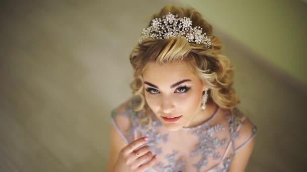 Krásná Módní nevěsta. Stylové vlasové doplňky. Blond kudrnaté vlasy. kadeřnický salon, stylový, módní stylové světlé make-up. Hezká žena pózuje, při pohledu na fotoaparát
