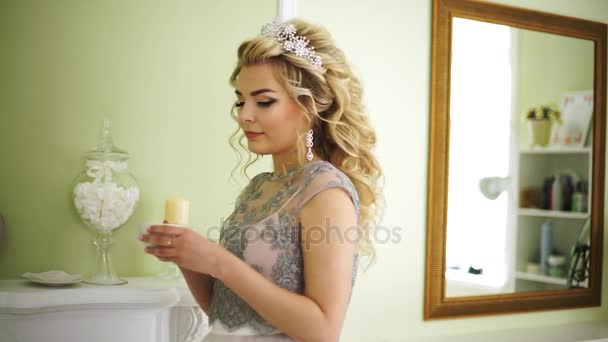 Bride takes a cup of coffee from the mantelpiece and takes a sip.