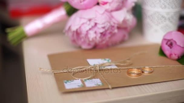 Krásné snubní prsteny leží na obálce na pozadí kytici květin.