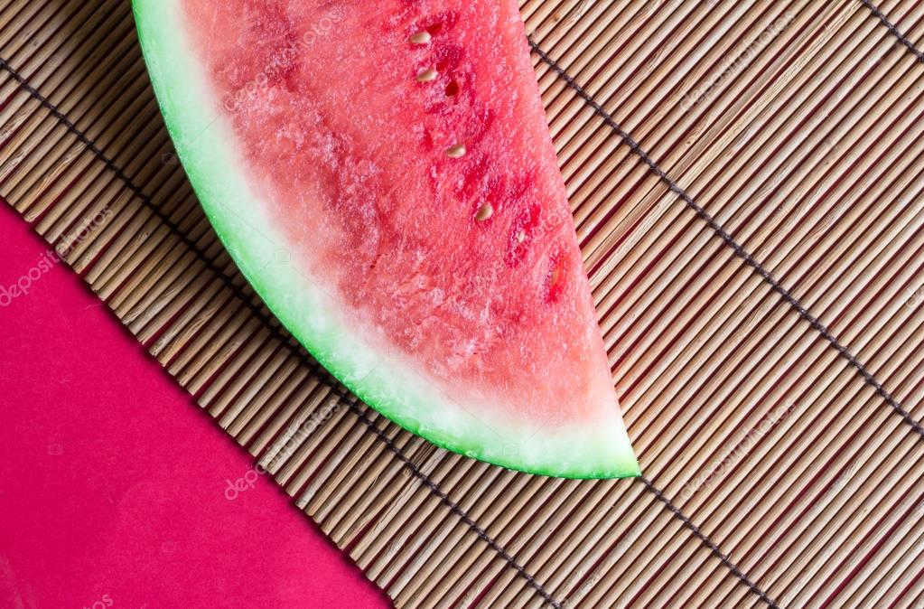 Watermelon slice on reed tablemat with red background close up