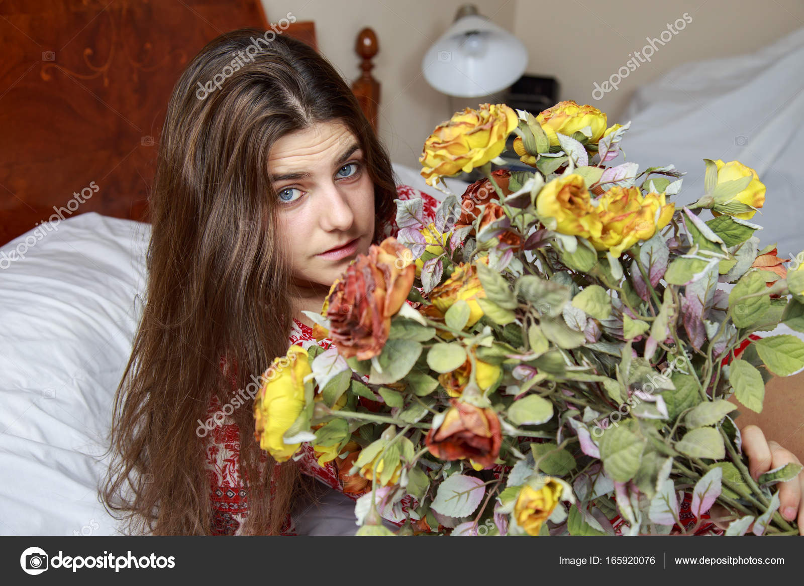 Beautiful young caucasian girl with blue eyes lying on the bed holding a  bouquet of dried flowers. The bed has white sheets and she is wearing a  dress with ... 892eb53ed