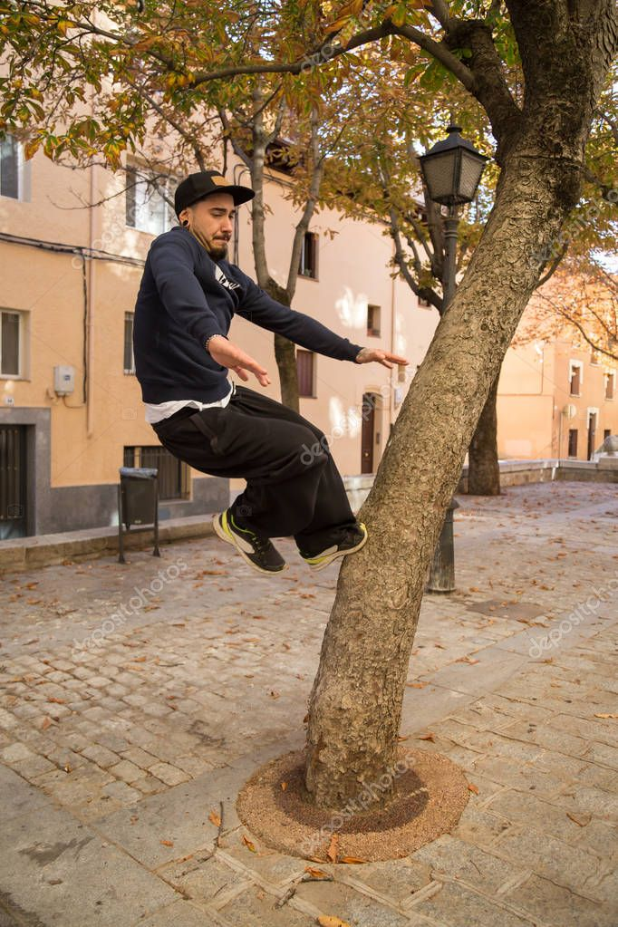 Young man doing an amazing parkour trick on a tree in the street.