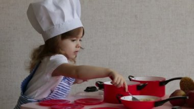Portrait cute little girl dressed as a chef cook food