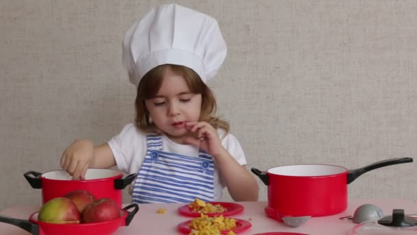 Portrait Adorable little girl in chef hat cook food