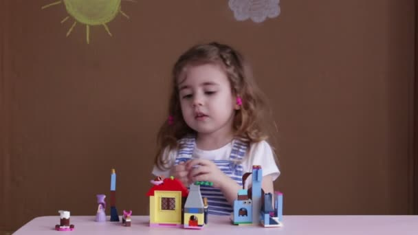 Cute funny preschooler little girl playing with construction toy blocks building a tower in kindergarten room.