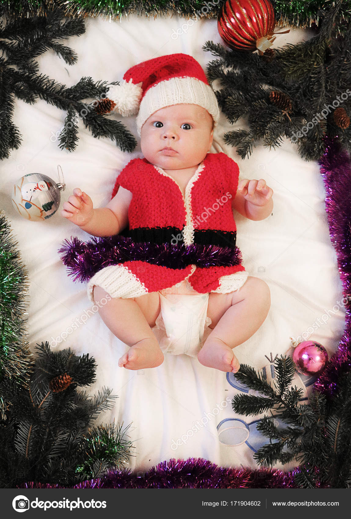 66818f8b2c458 Baby first christmas. Beautiful little baby in Santa hat and jacket  celebrates Christmas. New Year s holidays. Baby with santa hat inside  tinsel