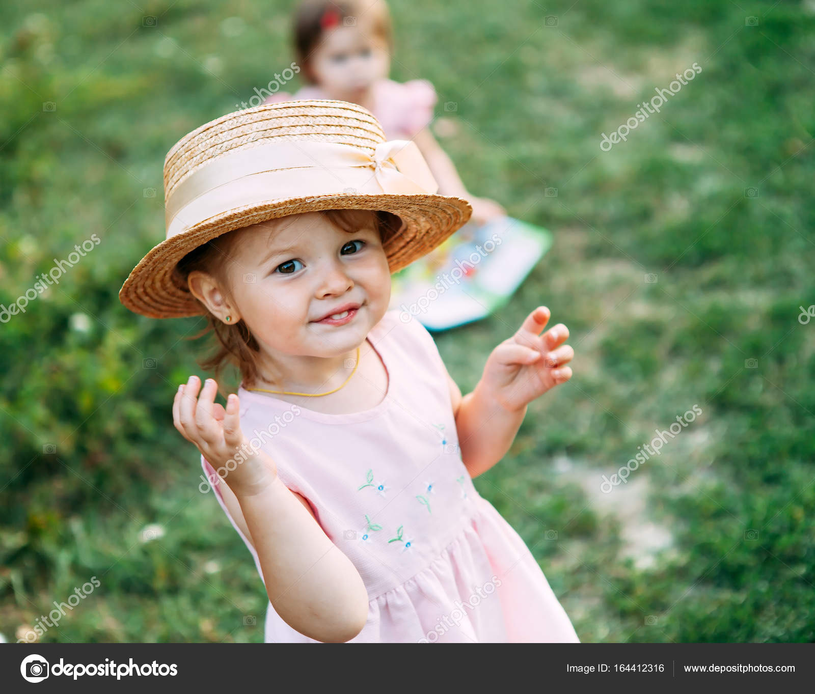 cute baby girl portrait.little girl in a straw hat smiles and looks