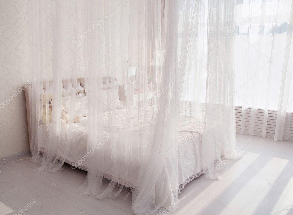 Slaapkamer met een witte bed grote spiegel in de buurt van het