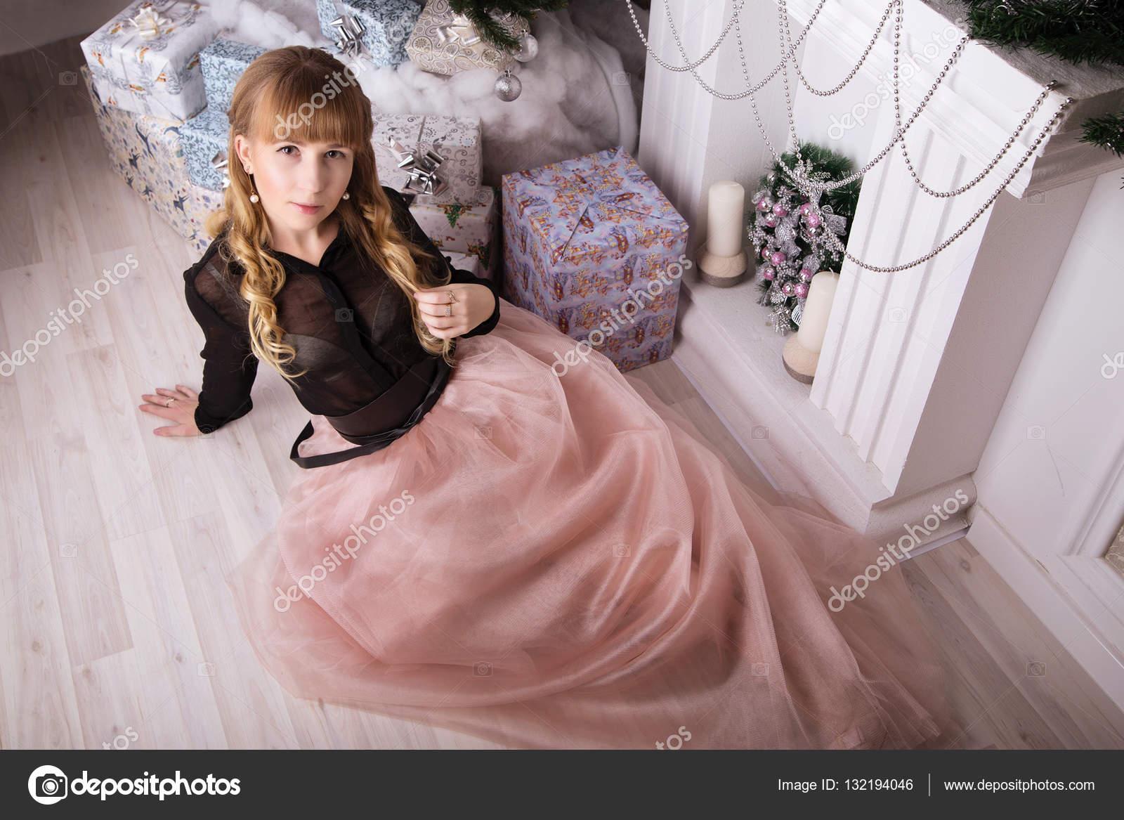 Joven hermosa mujer en vestido de noche elegante sentado en el piso ...