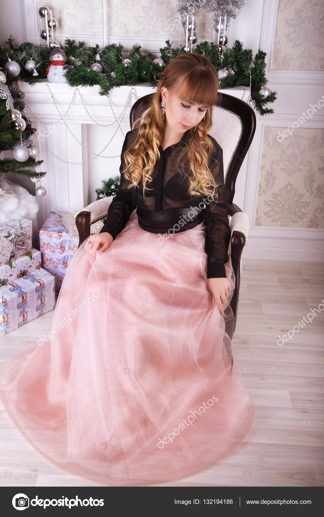Joven hermosa mujer en vestido de noche elegante sentado en silla ...